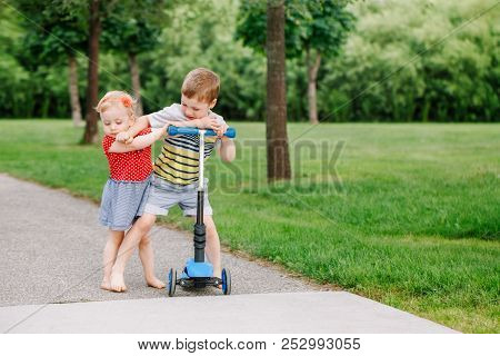 Two Little Caucasian Preschool Children Fighting Hitting Each Other. Boy And Girl Can Not Share One