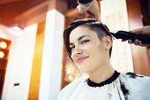 Beauty, hairstyle, treatment, hair care concept, young woman and hairdresser cutting hair at hairdressing salon. Hairdresser cuts beautiful girl's hair. Hairstylist serving client at barber shop poster