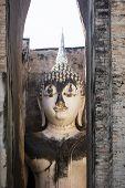 Ancient buddha statue in Wat Si Chum. Sukhothai Historical Park, Thailand poster