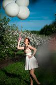 Girl with a charming smile holding a bunch of white helium balloons in her hand in a funny posture in a blossoming garden poster