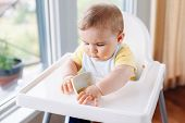 Portrait of cute adorable Caucasian child boy with dirty messy face sitting in high chair eating apple puree with fingers. Everyday home childhood lifestyle. Infant trying supplementary baby food poster