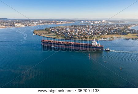 A Coal Ship Is Brought Into Port By Tug Boats In Newcastle Nsw Australia. Newcastle Is One Of The Bu
