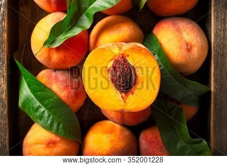 Peaches With Leaves In A Wooden Box With Peach In Halves On Top. Flat Lay Composition With Ripe Juic