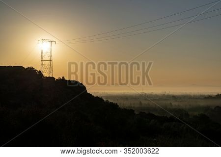 Electric power tower sunrise hilltop at Santa Susana Pass State Historic Park in Los Angeles California.