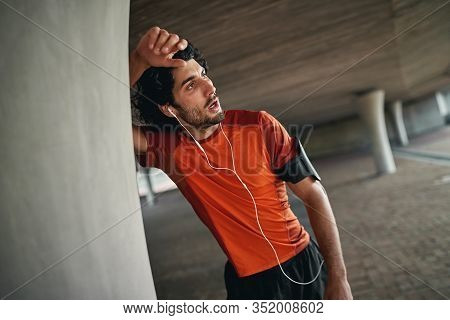 Exhausted Sporty Athletic Young Man With Earphones And Armband Leaning On Column Under The Bridge Ta