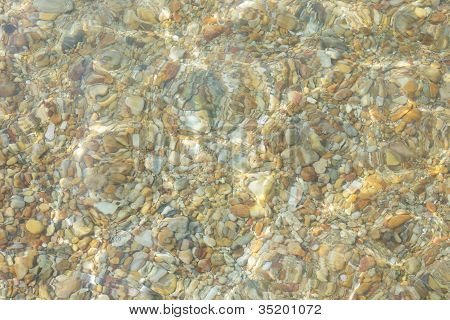 Pebbles under water in the summer time
