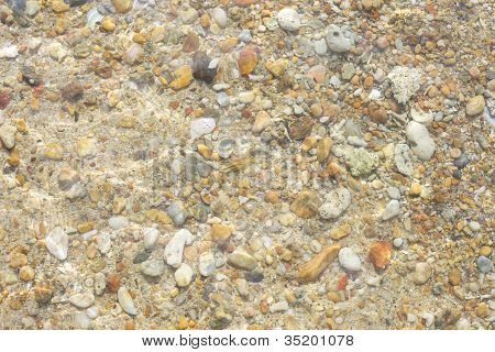 Pebbles corals and sand under water