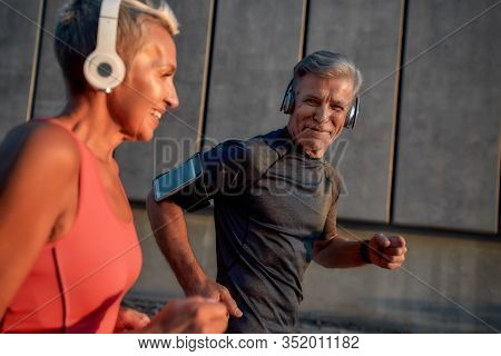 Yes, We Run Together. Happy And Healthy Middle-aged Couple In Headphones Running Together Through Th