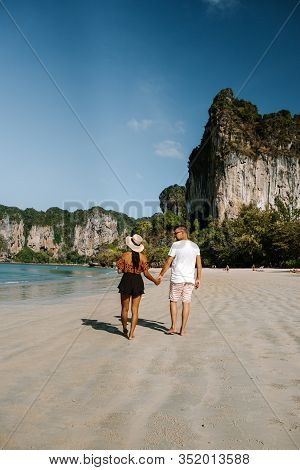 Railay Beach Krabi Thailand, Couple Walking In The Morning On The Beach With Tropical Cliffs And Lon