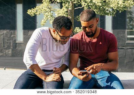 Excited Male Friends Studying Mobile App Features On Phone. Two Men In Casual Sitting On Parapet Out
