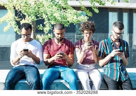 Group Of People Focused On Their Smartphones Sitting Outside. Men And Woman Sitting On Parapet And U