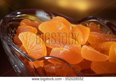 Pieces Of Marmalade Are In A Glass Vase. Vase And Marmalade In The Spotlight. Background With Lights