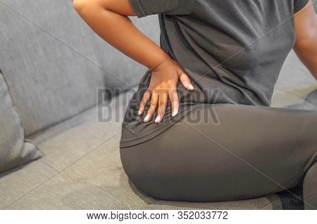 African Female Suffer From Low Back Pain. Hand Of African Woman Holding Her Waist Backache In Pain.