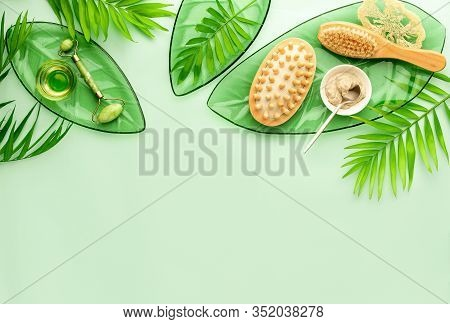 Spa Setting Background With Ready To Use Cosmetic Clay And Massage Brushes, Top Down View Image, Bla