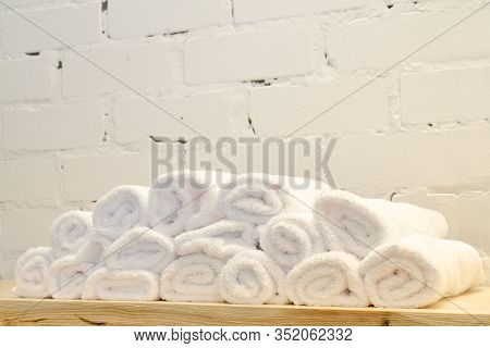 White Terry Towels, Rolled Up In Rolls, Lie On A Wooden Table Against A Brick Wall In A Barbershop F