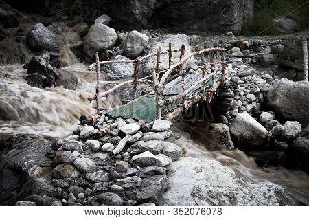 Wooden Bridge Over A Turbulent River In Mountain Range