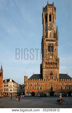 BRUGES, BELGIUM - MAY 28, 2018: Belfry tower famous tourist destination and Grote markt square in Bruges, Belgium with pedestrians and bicycle on sunset