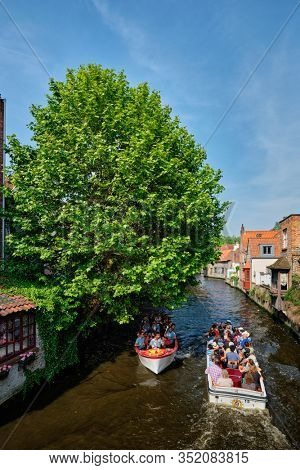 BRUGES, BELGIUM - MAY 28, 2018: Tourist boats with tourists in canal between old houses. Brugge Bruges, Belgium