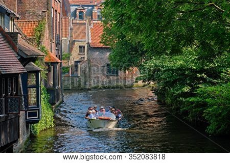 BRUGES, BELGIUM: Tourist boat with tourists in canal between old houses. Brugge Bruges, Belgium