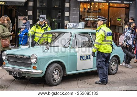 London, January 26, 2020. Policemans Standing By His Police Car.police Sign On An Austin Patrol Car.