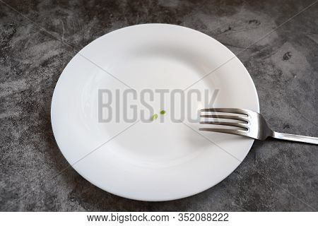 Empty White Plate With Small Peas And A Metal Fork On A Gray Background. The Concept Of Anorexia, We