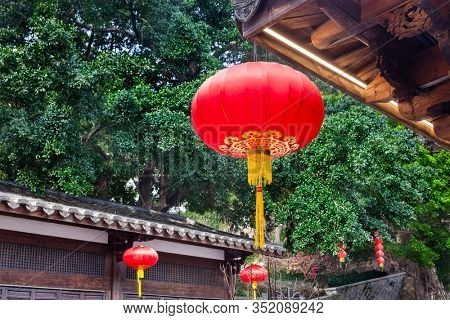 Beautiful red Chinese lantern hanging on eaves of  traditional Chinese old style Chinese wood  building to decorated the Chinese festive holiday in a park,Fuzhou,Fujian,China
