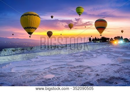 Hot Air Balloons And Natural Travertine Pools At Sunset In Pamukkale, Turkey.
