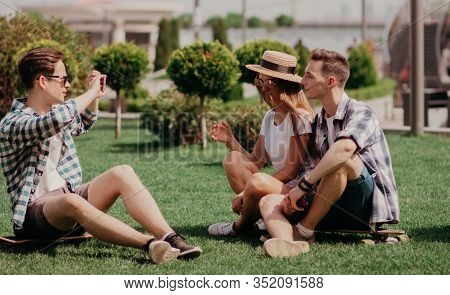 Students Take Photos Sitting On The Grass In A City Park. Light-skinned Youth Posing For A Photo On