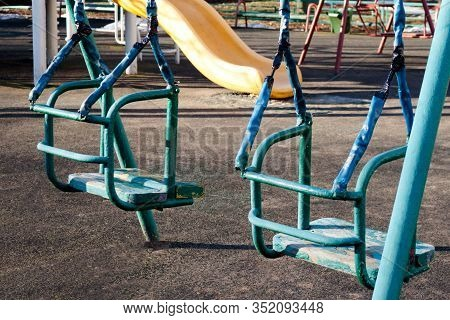Old Shabby Empty Swings At Background Of Desolate Children Playground Close Up View. Loneliness, Sad