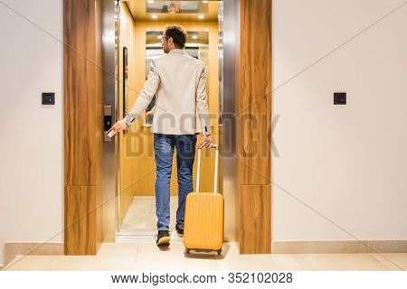 Modern Businessman Entering The Elevator With Luggage. Business And Travel Concept.