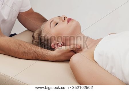 Osteopath Makes Head And Neck Massage To A Girl On A White Background