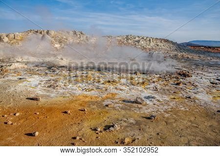 Geothermal Area Namafjall Hverir, Iceland. The Area Around The Boiling Mud Is Multicolored And Crack
