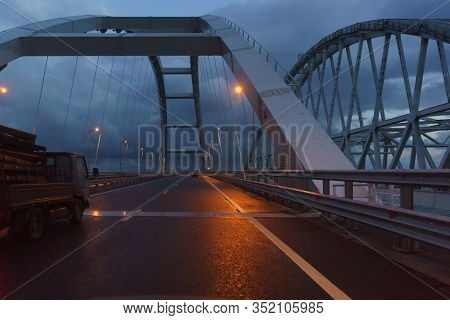 A Truck Rides Under The Arches Of The Crimean Bridge In The Late Evening. Lights Are On. Dull