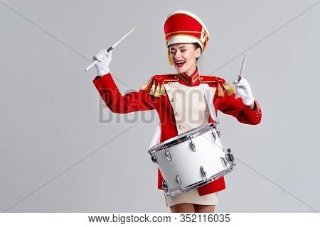 Drummer In A Red Uniform Drums On A Drum, Show Program And Celebration. Funny Drummer Plays Drums An