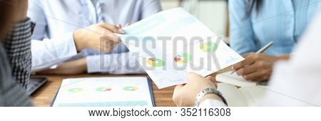 Close-up Of Male Hand Giving Documents With Diagram And Graph To Woman In Blue Blouse. Biz Team Disc