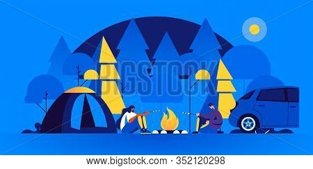 Pair Of Tourists Sitting Near Bonfire And Cooking Marshmallow In Camping At Night. Man And Woman At