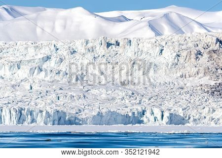 Glacier and pristine snow covered mountains in Nordfjorden, Svalbard.