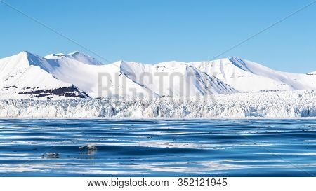 Panoramic view of a glacier and pristine snow covered mountains in Nordfjorden, Svalbard.