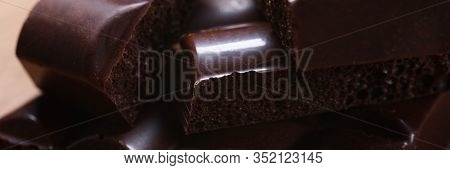Close-up Of Dark Chocolate Square Stack Made Of Bitter Cocoa Beans. Brown Delicacy Emanating Temptin