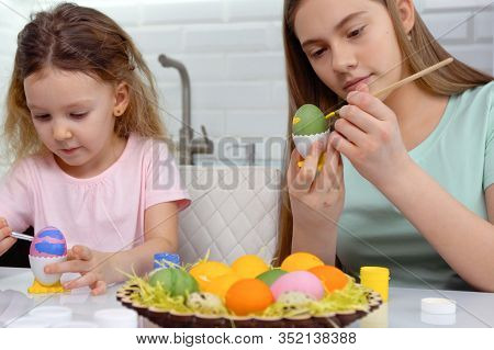 Happy Easter. Two Sisters Painting Easter Eggs. Happy Family Children Preparing For Easter. Cute Lit