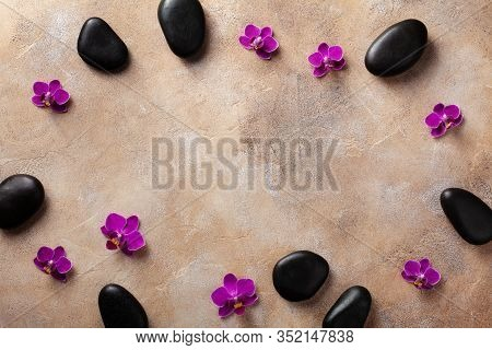 Spa Composition With Flowers And Massage Stone On Brown Background Top View. Beauty Treatment And Re