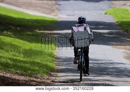 Rear View Of An Uber Eats Courier On A Bicycle In Brisbane. Uber Eats Is An American Online Food Ord