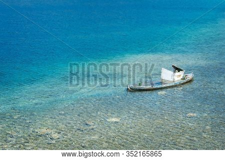 Old Forgotten Wooden Boat Rotting In The Shallow Turquoise Waters Of The Bay. Transparent Blue Water