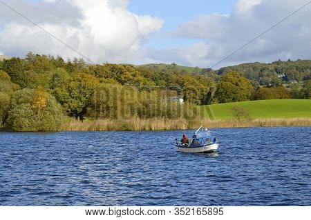 Lake Windermere, Cumbria, England, Uk - October 12, 2019 : A Man Fishing From A Boat On Lake Winderm