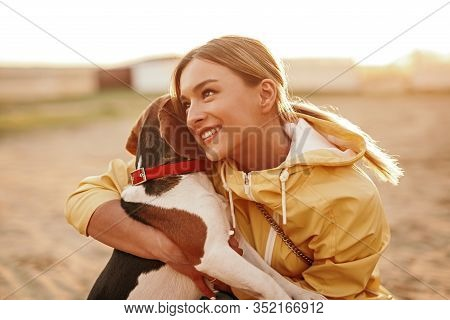 Optimistic Young Woman In Casual Clothes Smiling And Looking Away While Embracing Beagle In Evening