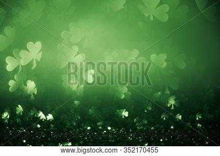 Green St Patricks day background with sparkling shamrock shapes