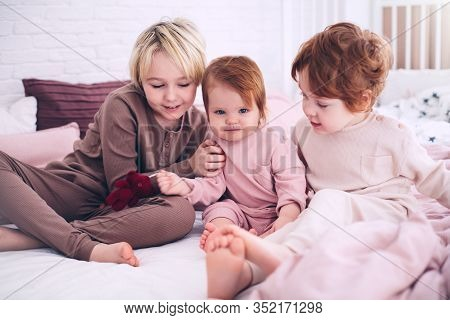 Cute Happy Kids, Siblings Sitting Together On The Bed In The Morning, In Pajamas