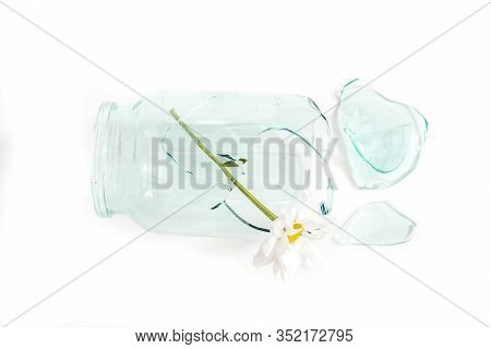 Fragment Of One Glass Jar Damaged Cracked And Cracked, Splinters On A White.two Flowers Ka Symbol Of