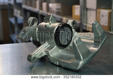 Front brake caliper close-up on a steel background. Original high-quality spare parts for a modern c