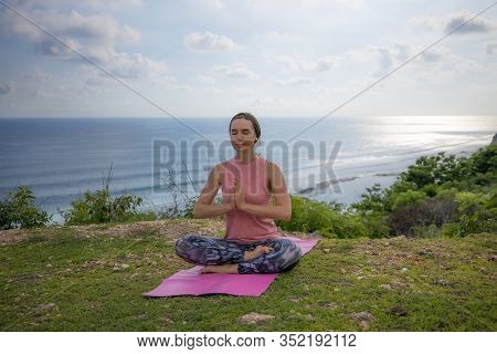 Young Caucasian Woman Sitting On Yoga Mat, Meditating, Practicing Yoga And Pranayama. Hands In Namas